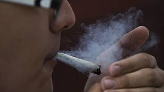 شاب يدخن الماريجوانا أمام مبنى مجلس الشيوخ المكسيكي في مكسيكو سيتي.