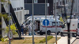 عاملون طبيون ينقلون مريضًا يشتبه في إصابته بفيروس كورونا على نقالة في مستشفى في كوموناركا، خارج موسكو- روسيا.