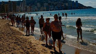 La gente camina por la playa en un día de verano en Benidorm, sureste de España, el viernes 25 de junio de 2021.