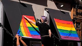A woman hangs rainbow flags on the outside of a restaurant on the first day of the annual LGBT+ pride week in Madrid.