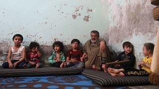 النازح السوري مصطفى شعبان أبو خليل يجلس بين أطفاله في منزلهم في مدينة الباب شمال غرب حلب، شمال سوريا، 23 يونيو 2021
