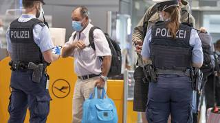 Federal police officers check passengers arriving aboard a flight from Portugal, at Frankfurt airport, Germany, Tuesday June 29, 2021.