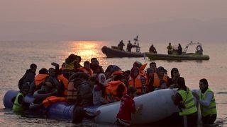 متطوعون يساعدون لاجئين ومهاجرين عند وصولهم إلى شاطئ جزيرة ليسبوس اليونانية بعد عبور بحر إيجه من تركيا، الأحد 20 مارس 2016