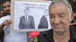 A man holds a carnation during a rally called by Roma organizations to honor a Roma man Stanislav Tomas who died after police officers held him in the Czech Republic.