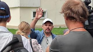 Roman Badanin, chief editor of the Proekt investigative online outlet, waves journalists as he departing to police station in Moscow, Russia, Tuesday, June 29, 2021.