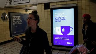 A poster encourages EU nationals to apply to the Government's post-Brexit EU settlement scheme  at South Kensington underground station in London on March 25, 2019.
