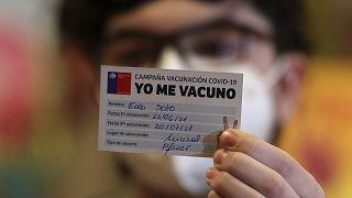 Un joven sujeta un carnet de la campaña Yo Me Vacuno