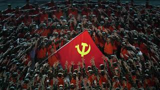 Performers gather around a Communist Party flag during a gala ahead of the 100th anniversary of the founding of the Chinese Communist Party in Beijing on June 28, 2021.