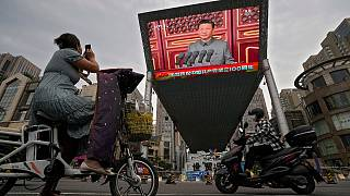 A woman films a large video screen showing Chinese President Xi Jinping's speech commemorating the 100th anniversary of China's Communist Party, Beijing, July 1, 2021.