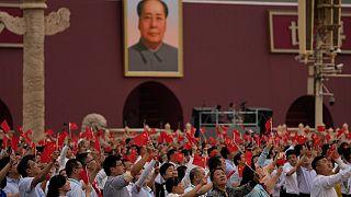 صينيون يلوح بالأعلام وصورة كبيرة لماو تسي تونغ خلال حفل بمناسبة الذكرى المئوية لتأسيس الحزب الشيوعي الصيني في بكين.