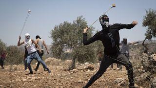 فلسطينيون يستخدمون المقلاع لرشق الحجارة خلال احتجاج على البؤرة الاستيطانية التي أقيمت في قرية بيتا الفلسطينية.