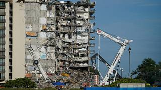 Workers peer up at the rubble pile at the partially collapsed Champlain Towers South condo building, on Thursday, July 1, 2021, in Surfside, Florida.