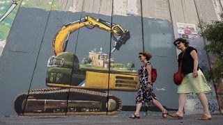 سائحون يمرون بجانب لوحة جدارية تصور جنديًا إسرائيليًا مع جرافة على وشك هدم منزل فلسطيني، رسمها الفنان الفلسطيني تقي سباتين