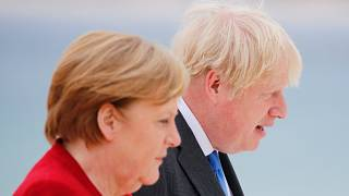 Britain's Prime Minister Boris Johnson and German Chancellor Angela Merkel (L) look on as they arrive for the G7 summit in Carbis Bay, Cornwall, on June 11, 2021.