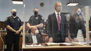المديرُ المالي لمنظمة ترامب، ألان وايسلبرغ، جالسٌ في المحكمة وخلفه ضابطا شرطة