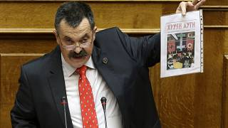 Golden Dawn's Christos Pappas shows a copy of his party magazine as he speaks to lawmakers during his time as a member of the Greek parliament, Athens, June 4, 2014.