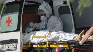 """عاملون في القطاع الطبي الروسي ينقلون مصاباً بـ""""كوفيد-19"""" إلى إحدى المشافي القريبة من العاصمة موسكو"""