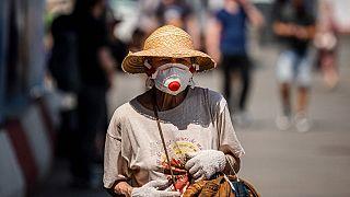 A woman wearing a face mask, walks down a street on June 21, 2021.