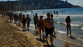 In this June 25, 2021, file photo, people walk along the beach on a summer's day in Benidorm, southeast Spain.