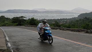 رجلان على دراجة نارية يغادران المنطقة القريب من بركان تال في مقاطعة باتانجاس بالفلبين حيث  تم إجلاء آلاف