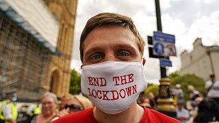 Londra'da meclis binası önünde Covid-19 kısıtlamalarını protesto eden bir kişi.