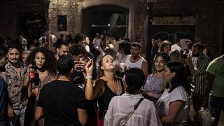 Un grupo de jóvenes está de fiesta nocturna en una concurrida calle de Barcelona.