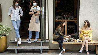 Due donne pranzano fuori da un bar, non potendo entrare perché senza un QR code che attesti l'avvenuta vaccinazione o un tampone negativo, a Mosca