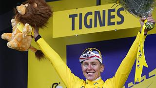 Slovenia's Tadej Pogacar, wearing the overall leader's yellow jersey, celebrates on the podium after the ninth stage of the Tour de France cycling race