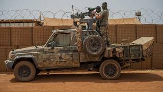 French Barkhane force commandos mount a machine gun on a camouflaged pickup as Malian workers drive by before heading on a mission from their base in Gao, Mali, June 7, 2021.