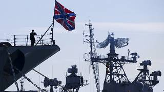 FILE: A Russian sailor salutes on the bow of Missile Cruiser Moskva, left, in Sevastopol, Crimea, Sunday, March 30, 2014.