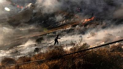 A firefighter douses the flames in an effort to contain a fire near the Kotsiatis area, on the outskirts of Cyprus' capital Nicosia.