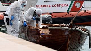 Italian forensic police inspect the damage on the couple's boat.