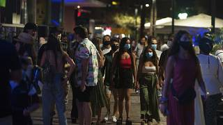 FILE: A group of people wearing face masks walk on the street In Fuengirola, near Malaga, Spain, Saturday, Aug. 8, 2020