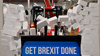 UK Prime Minister Boris Johnson drives a JCB through a symbolic wall during an election campaign event at a JCB plant, Uttoxeter, England, December 10, 2019.