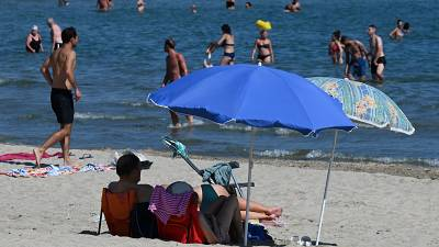 A man and a woman sit on the sand under a parasol on the beach in Palavas-les-Flots, southern France