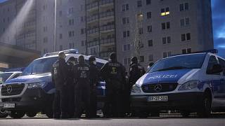 Federal German police forces stand in a parking lot in Berlin-Lichtenberg and prepare for a raid.