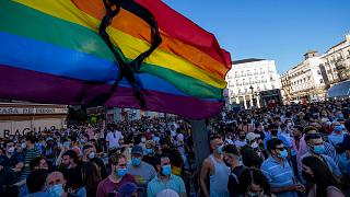 A rainbow emblem  with a achromatic  ribbon flutters during a protestation  connected  Monday successful  the Puerta del Sol successful  cardinal  Madrid.