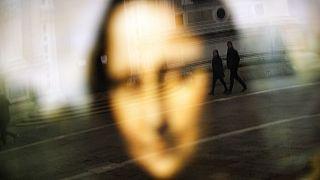 Da Vinci leghíresebb alkotása, a Mona Lisa plakátja előtt sétáló emberek