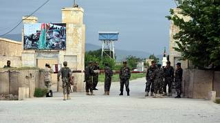 Afghan soldiers at the gate of a military compound after an attack by gunmen in Mazar-e- Sharif