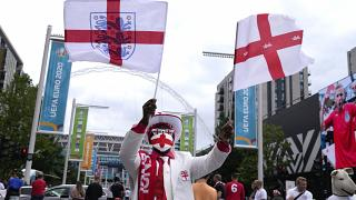 An England fan waves flags outside Wembley Stadium in London, Wednesday, July 7, 2021, ahead of the Euro 2020 soccer championship semifinal match between England and Denmark.