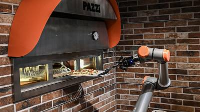 """This photograph taken on July 1, 2021, shows """"Pazzi"""", a pizza-making robot at work in a restaurant in Paris."""