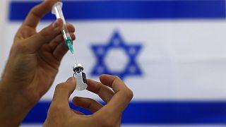 Un paramédico militar israelí prepara una vacuna COVID-19 de Pfizer