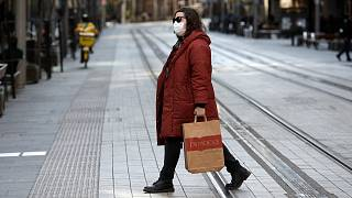 A woman crosses a normally busy street in Sydney, Wednesday, July 7, 2021