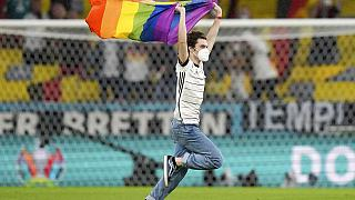 A fan with a LGBT pride flag runs on the pitch during the national anthems before the Euro 2020 soccer championship group F match between Germany and Hungary.