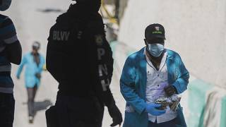 Um investigador da polícia do Haiti com um saco cheio de balas recolhidas no palácio presidencial