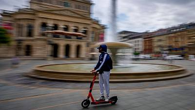 A man passes the Old Opera on an electric scooter in Frankfurt, Germany, Tuesday, June 22, 2021.
