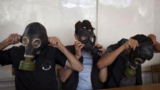متطوعون يرتدون أقنعة واقية من الغازات خلال فصل دراسي لشرح كيفية الاحتماء من أي هجوم كيماوي، في مدينة حلب شمال سوريا في 15 سبتمبر 2013.