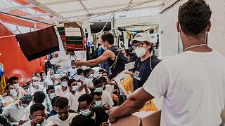 Staffers distribute food to migrants on the deck of the Ocean Viking rescue vessel.
