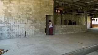 Devla Ajsic walking inside former Dutch U.N. compound where she survived sexual abuse in July 1995