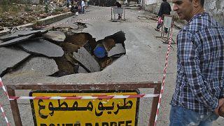 رجل يقف بجانب حفرة سببتها الأمطار الغزيرة بالعاصمة الجزائرية. 08/09/2020
